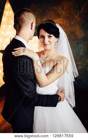 Charming bride and groom lovely embracing on their wedding celebration in an interior. Sensual hug.