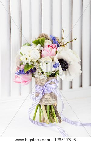 Bouquet from pink tulips violet grape hyacinths white anemones violet veronica and white buttercup with violet ribbon on white wooden stylish shutter background