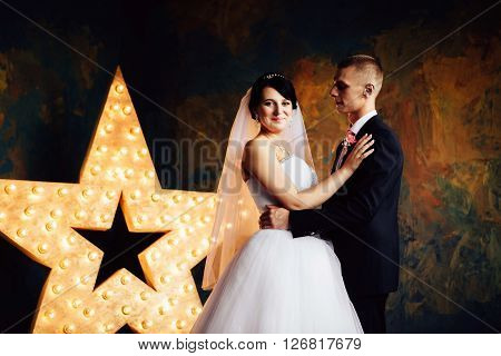 Charming bride and groom lovely embracing on their wedding celebration in an interior. Sensual hug. ** Note: Visible grain at 100%, best at smaller sizes