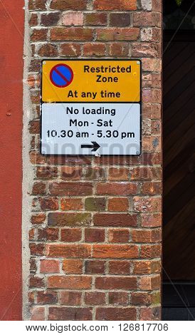 Restricted Zone At Any Time Sign on The Red Brick Wall and No Loading Times