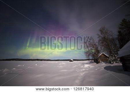 White sea shore under the lights of Aurora borealis. Northern Karelia. Russia.