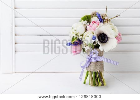 Bouquet from pink tulips violet grape hyacinths white anemones violet veronica and white buttercup with violet ribbon with white wooden shutter background