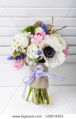 Bouquet from pink tulips violet grape hyacinths white anemones violet veronica and white buttercup with violet ribbon with stylish white wooden shutter background