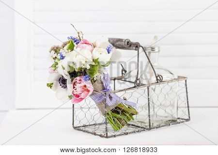 Bouquet from pink tulips violet grape hyacinths white anemones violet veronica and white buttercup with violet ribbon lying in the metal rustic basket with glass bottle on white shutter background