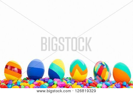 Close-up of different painted easter eggs on pile of candies. White background. Copy space