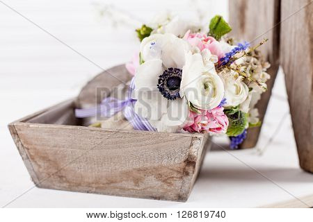 Bouquet from pink tulips violet grape hyacinths white anemones violet veronica and white buttercup with violet ribbon lying in the old wooden basket with white background