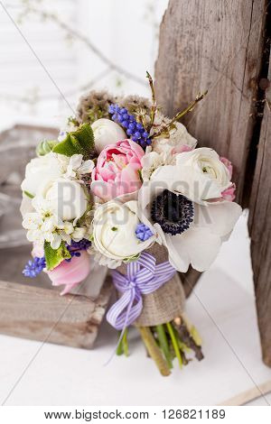 Bouquet from pink tulips violet grape hyacinths white anemones violet veronica and white buttercup with violet ribbon standing near the old wooden basket and bench with white background