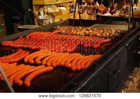 Street food. Pork sausages and kebabs are fried in large baking sheets on the street. The food at the Christmas fair in Budapest. Grilled sausages on Christmas market.