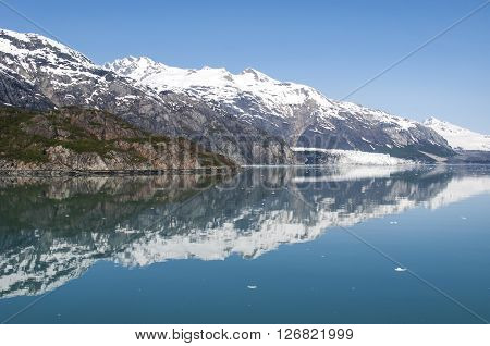 Mountains reflecting in still water of Glacier Bay. National Park Glacier Bay, Alaska, United States