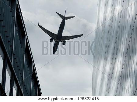 Passenger jet flying over buildings