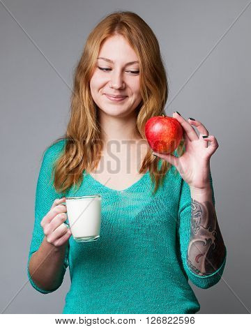 Portrait of a young ginger lady in turquoise blouse with red apple in one hand and a cup of milk in the other hand grey background
