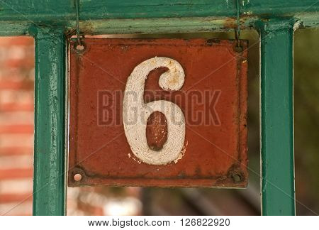 Old retro weathered cast iron plate with number 6