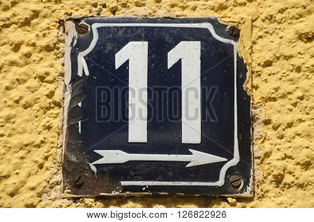 Weathered grunge square metal enameled plate of number of street address with number 11 closeup