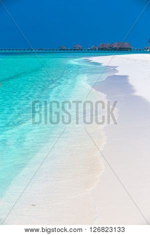 Tropical Island With Sandy Beach, Palm Trees, Overwater Bungalows And Tourquise Clear Water
