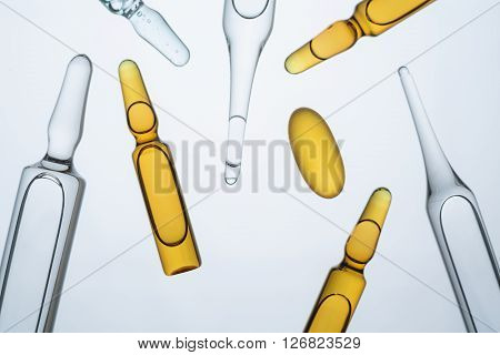 Many ampoules of different types and colours and yellow pill. Concept of medicine.