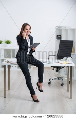 Smiling businesswoman in suit sitting on table holding notebook and speaking on phone tablet and coffee on table. Concept of work.