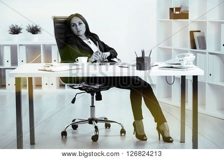 Black and white pictue of tired businesswoman sitting in swivel chair at office desk