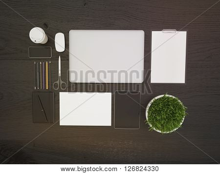 Topview of dark wooden desktop with closed laptop small plant and other office tools. Mock up 3D Rendering