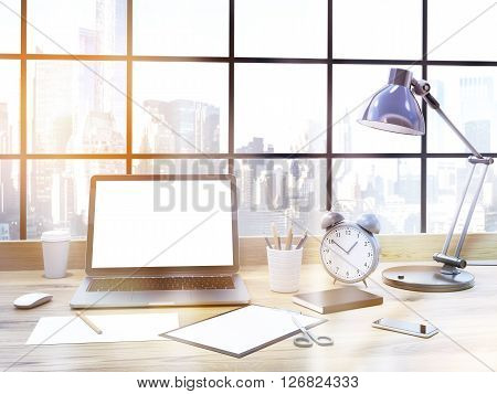Frontview of sunlit office table with blank laptop and other office items. New York cityscape background. Toned image. Mock up 3D Rendering