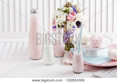 Four bottles of milkshakes three with straws and glass of milk and plates with pink and white meringues and cloth on white wooden shutter with bouquet from pink tulips violet grape hyacinths white anemones violet veronica and white buttercup with violet r