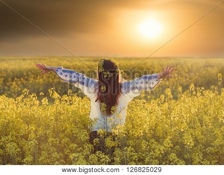 Portrait of a young woman in a rapeseed field. Young girl wearing traditional romanian blouse