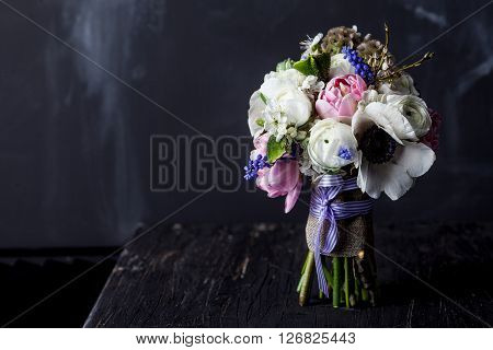 Bouquet from pink tulips violet grape hyacinths white anemones violet veronica and white buttercup with violet ribbon standing on black old wood with blackboard in the background