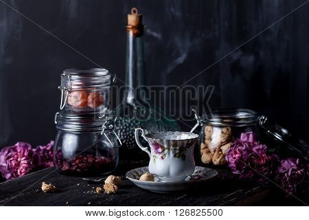 White floral tea cup and jars with cookies dryed cranberries candied kumquat and bottle of liqueur and pink cloves on black old wood on blackboard background