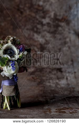 Bouquet from pink tulips violet grape hyacinths white anemones violet veronica and white buttercup with violet ribbon standing on rought metal background with rust