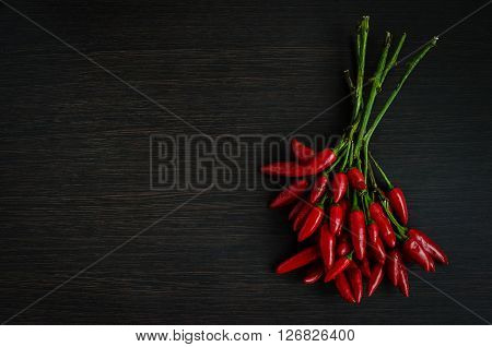 Red hot mini chili peppers over dark wooden background with place for text. Overhead view of chili pepper on wood background. Dark food photography with bunch of red chili. Top view. Copy space.