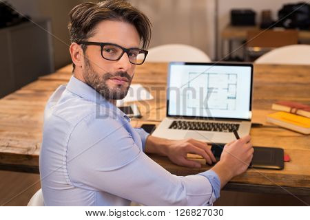 Portrait of a young interior designer working at office. Man working on laptop turning around towards camera. Happy architect studying layout on laptop at desk and looking at camera with satisfaction