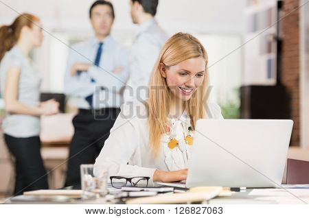 Business woman in office using laptop. Portrait of busy secretary typing on keyboard. Portrait of happy smiling young businesswoman working on laptop with her colleagues in background.