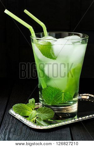The Martini cocktail with green tea mint and ice in a glass with cocktail straw on a dark background