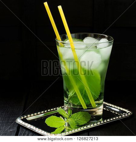 The Martini cocktail with green tea mint and ice in a glass with cocktail straw on a dark background. Square image