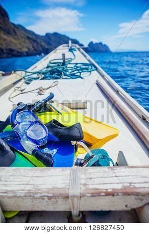 Scuba mask with yellow flippers on wooden boat background