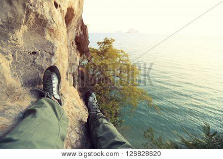 rock climber legs sit at seaside rock