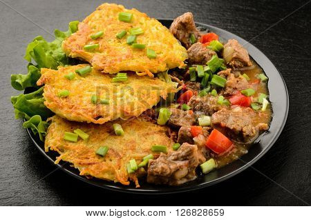 Potato pancake with goulash on table- hungarian cuisine.