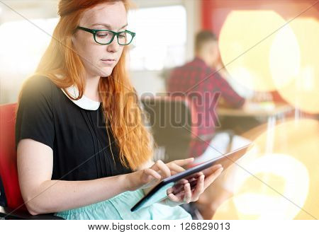 Casual portrait of a redhead business woman using technology in a bright and sunny startup with the team in the background