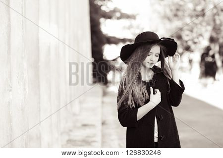 Beautiful teenage girl 14-15 year old wearing stylish winter coat and hat outdoors. Elegance.