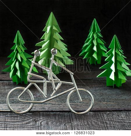 Healthy lifestyle concept. Metal figures cyclists and paper spruce origami as an illustration sports. Selective focus square image