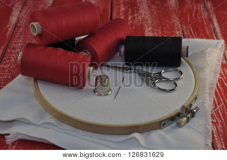 items for sewing and embroidery on the background of a red wooden table