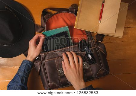 Preparing vintage bag to travel. Men's hands, vintage hat, bag, diary and sungalsses