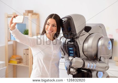 Say cheese. Cheerful beautiful  nice woman holding cellphone and making selfies  with the robot
