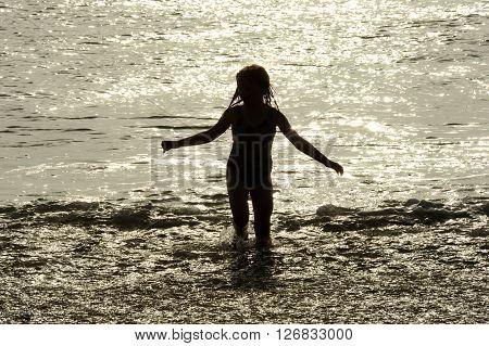 Children playing in sunlit sea in summer
