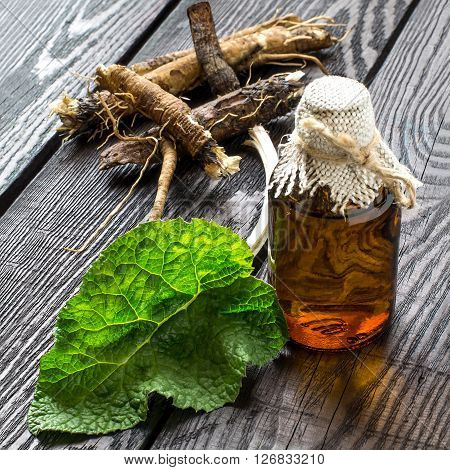 Medicinal plant - a burdock. The roots and leaves of burdock burdock oil in bottles on a wooden background. It is used for the treatment and care of hair. Selective focus square image