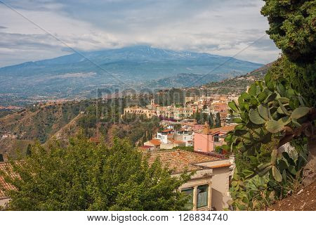 View of Taormina from the greek amphitheatre with the Etna Volcano in the back in Sicily Italy