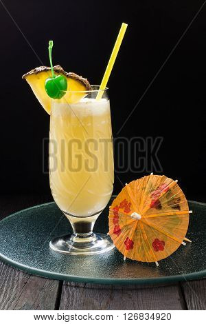 Refreshing pineapple cocktail with coconut in glass with slices of pineapple green cocktail cherry straws and decoration for glasses in the form of a umbrella