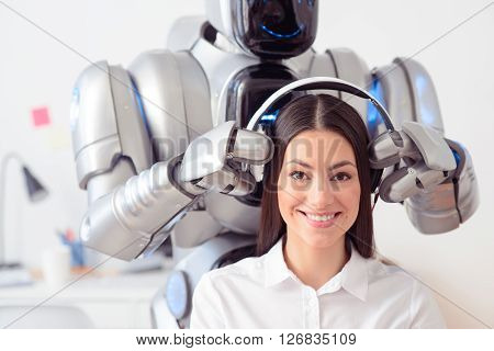 Thats a nice day. Cheerful delighted  pretty girl smiling while the robot wearing headphones on her ears