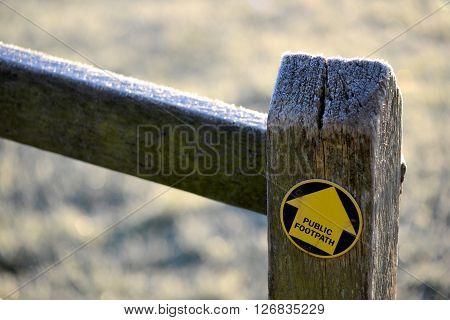 Yellow footpath arrow on oak fence post