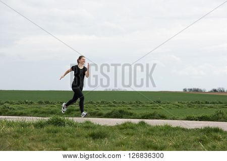 pretty young woman  in black jogging (running) outdoors
