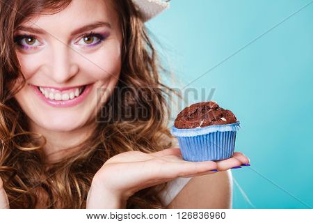 Sweet food sugar make us happy. Smiling woman curly hair holds cake chocolate muffin in hand blue background